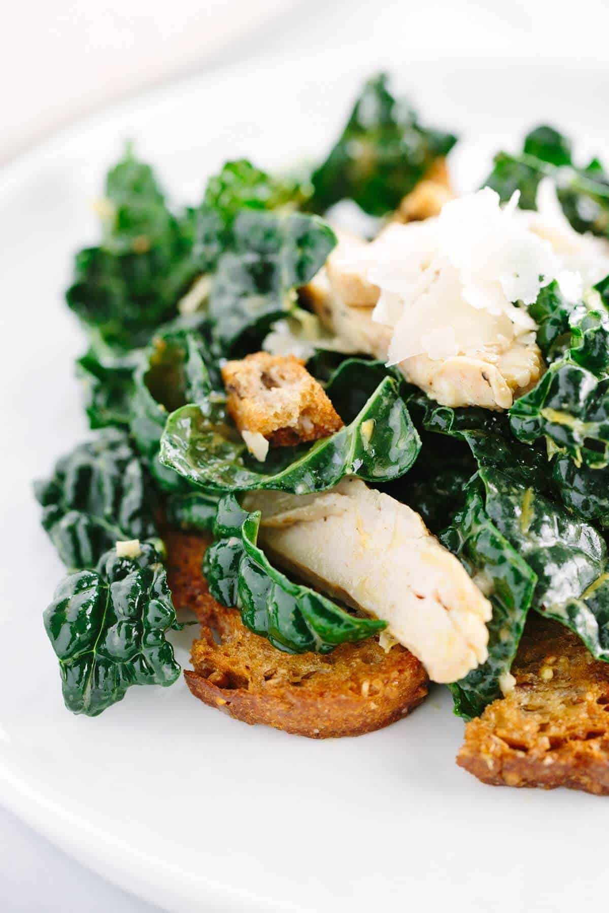 Chicken Kale Caesar Salad with Croutons - Fast and healthy recipe! Tender kale leaves tossed in light lemon anchovy dressing and topped with homemade whole grain croutons. | jessicagavin.com