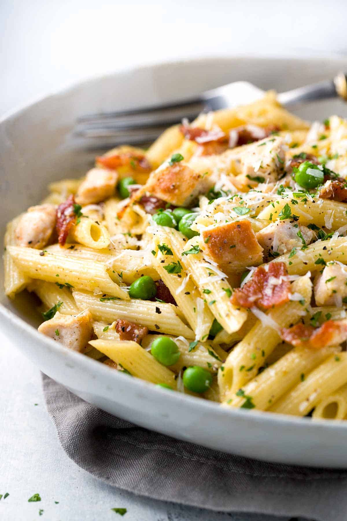 One Pan Chicken Carbonara Penne Pasta- A comforting classic Italian pasta recipe! Tender penne tossed in a luscious parmesan sauce with bacon and peas. | jessicagavin.com