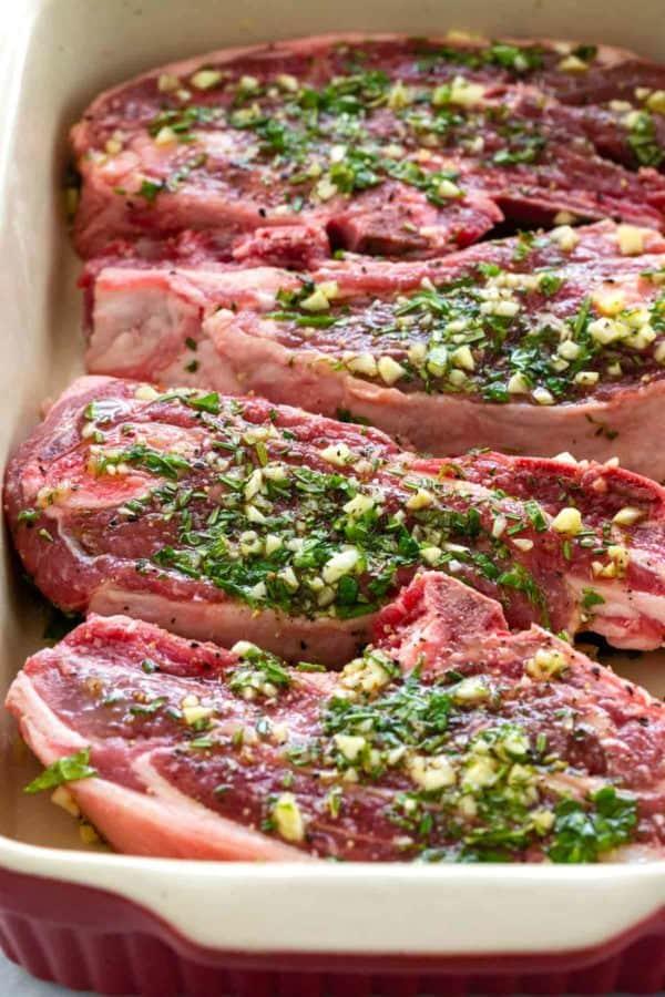 raw lamb chops marinating with garlic and rosemary