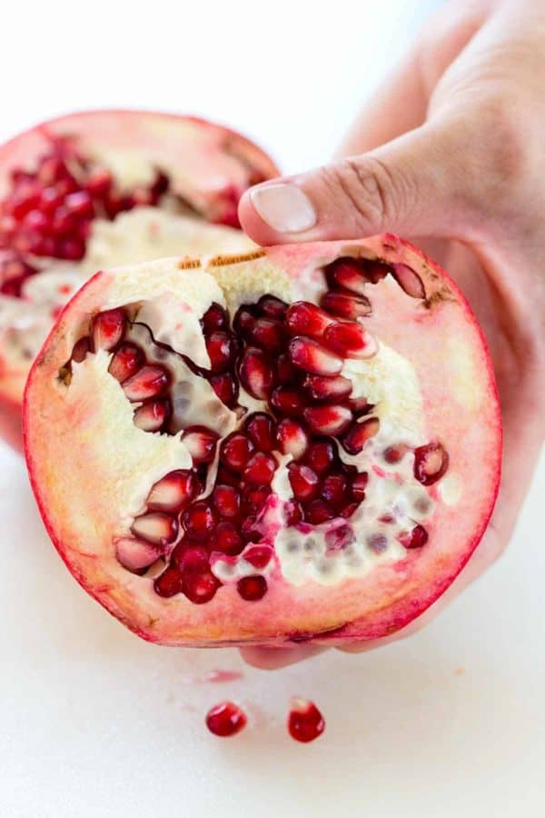 Hand separating a pomegranate fruit to reveal the seeds inside