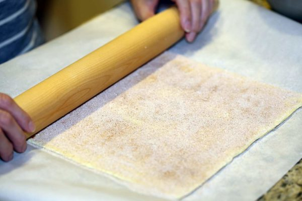 Using rolling pin to smash sugar into the dough