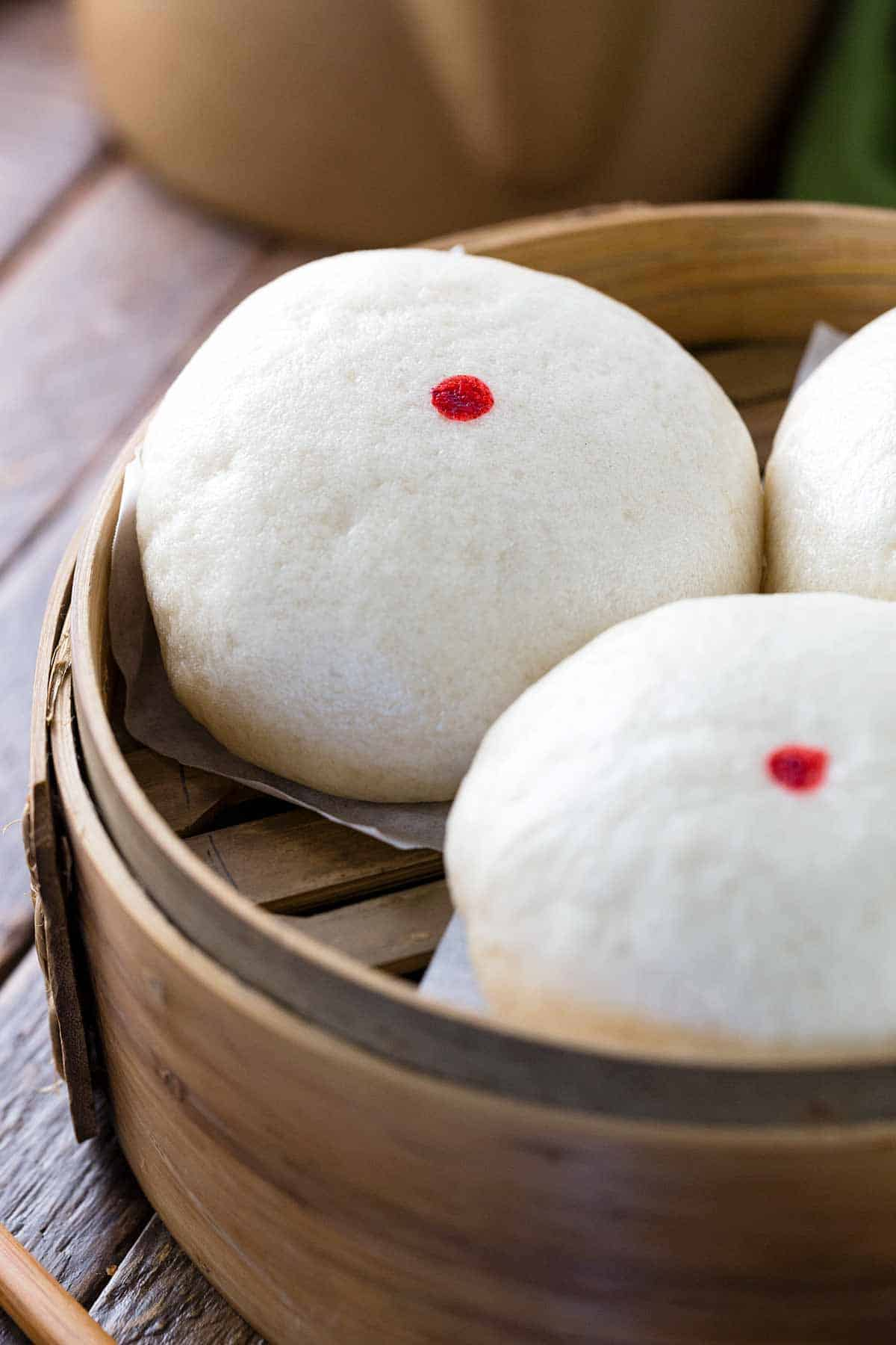 Chinese custard buns with red dots in a wooden steamer basket
