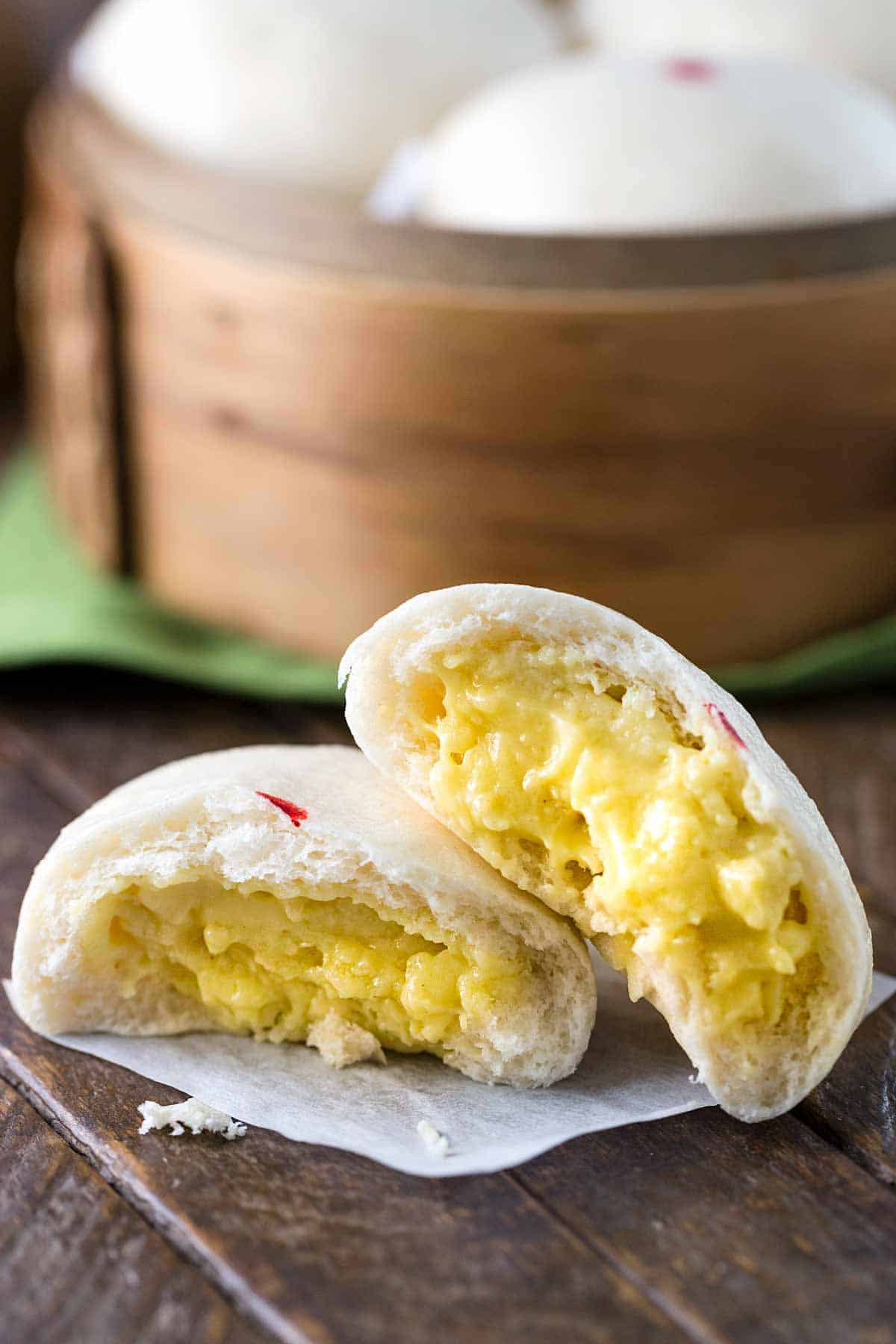 Chinese steamed buns torn in half showing the custard filling