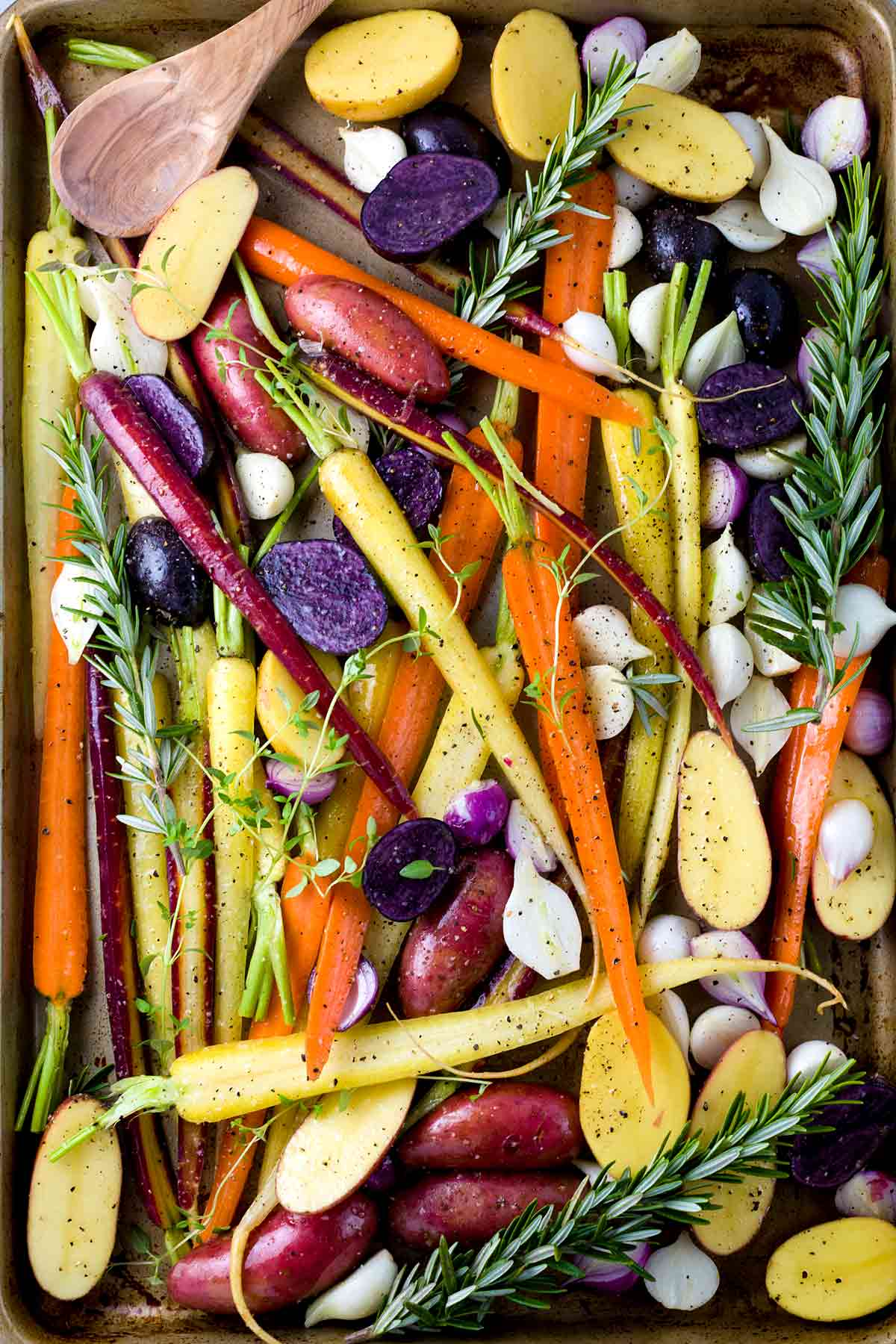 Rosemary, thyme, potatoes, carrots, and onions on a sheet pan
