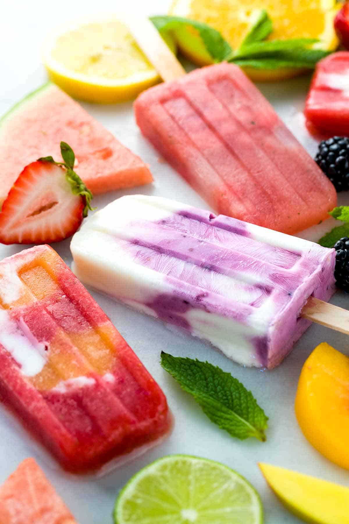 Brightly colored homemade fruit popsicles on table with fruit slices