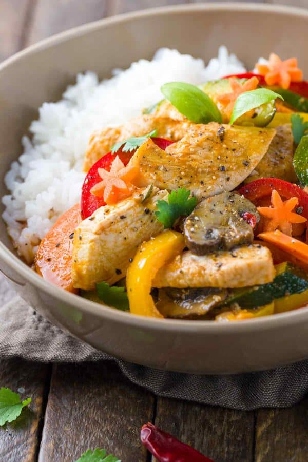 Bowl of white rice and Thai chicken curry with vegetables