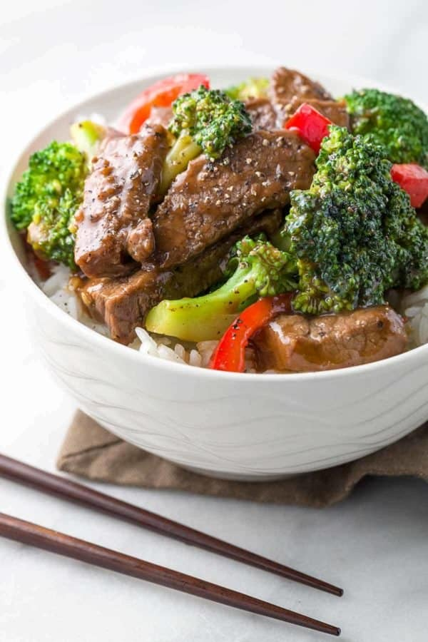 White bowl of broccoli beef stir-fry on a table with chopsticks