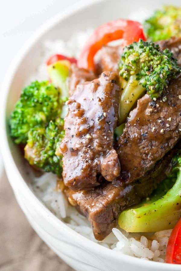 Closeup photo of tender pieces of beef and broccoli over white rice