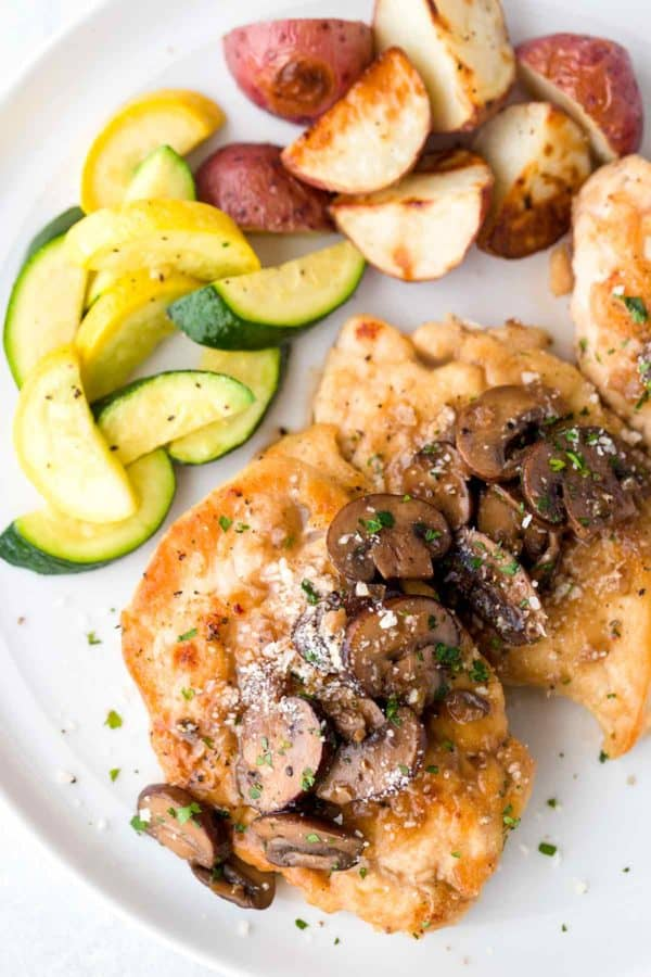 Top down view of a plate of chicken marsala served with vegetables and potatoes