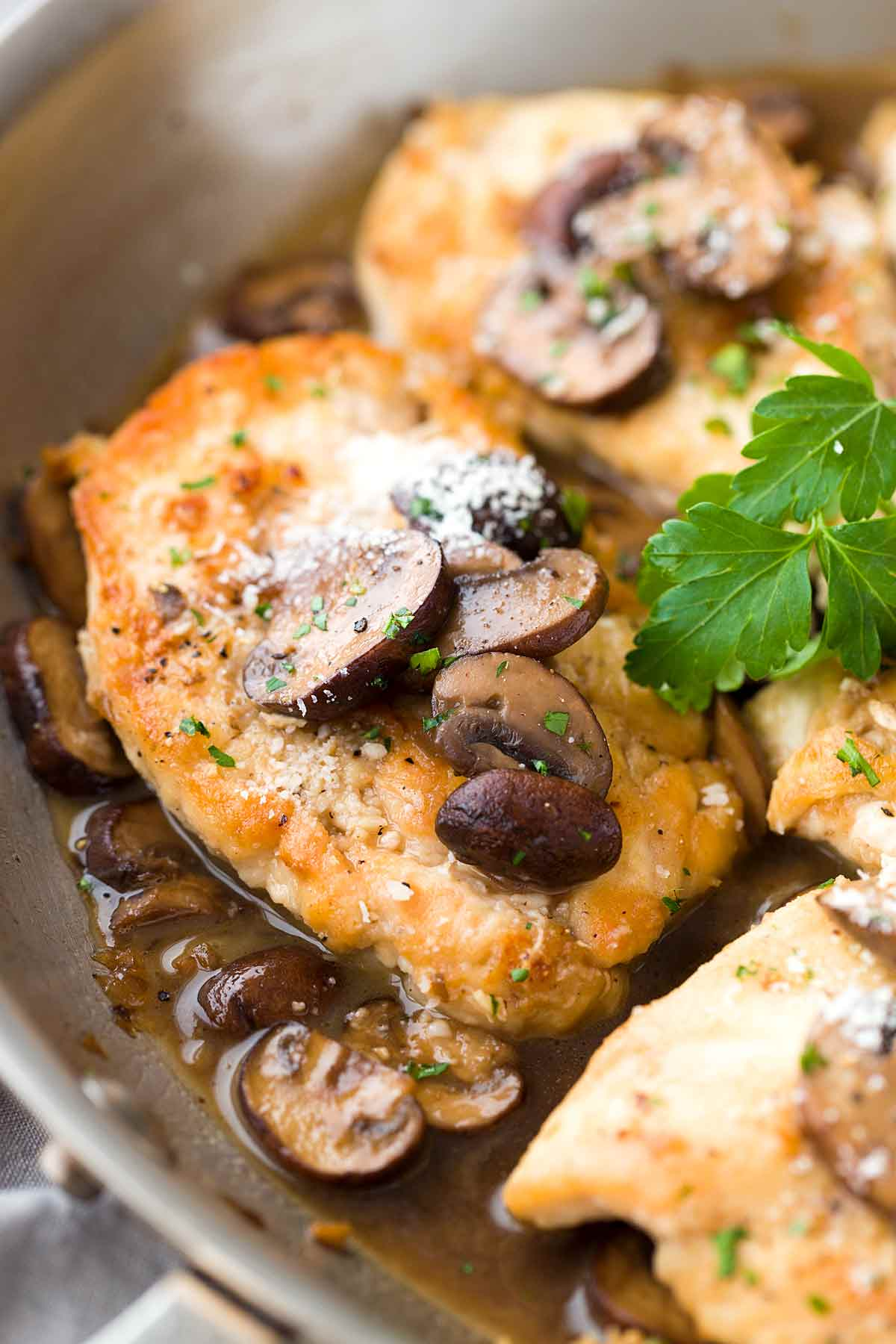 Lightly browned chicken simmering in a sweet marsala wine sauce