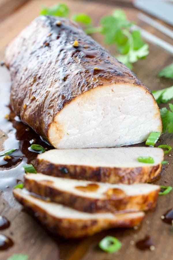 Pork tenderloin being sliced open on a cutting board