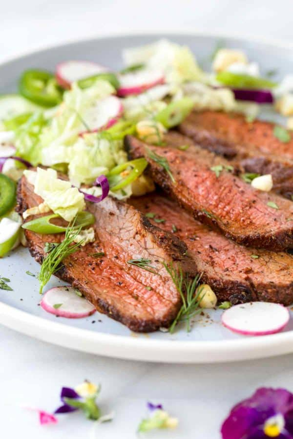 Slices of tri tip steak on a plate with lettuce and red onions