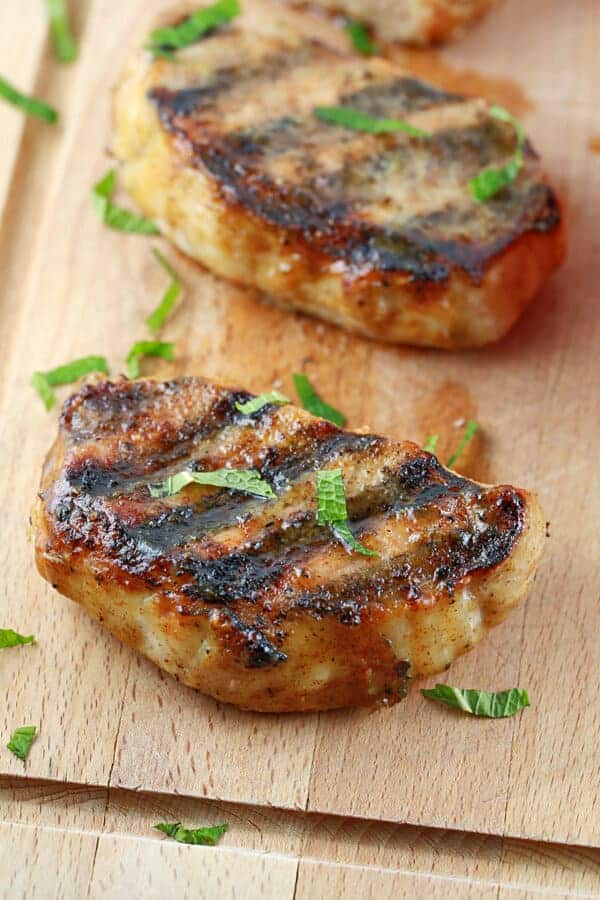 Two grilled pork chops with honey mustard glaze on a cutting board