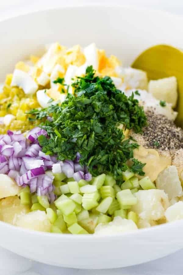 chopped onions, celery and pieces of potatoes and eggs in a white bowl