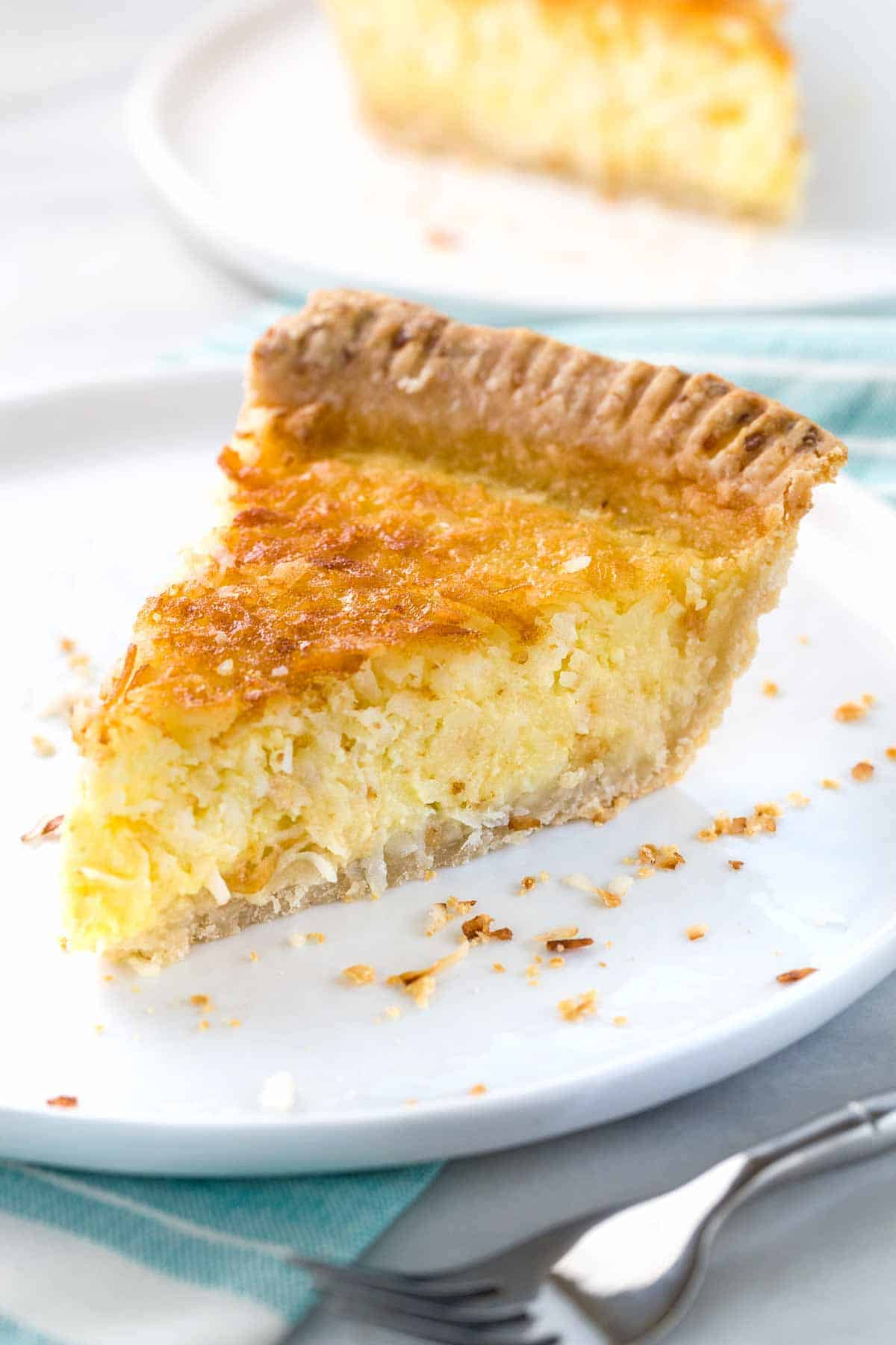 Slice of coconut custard pie with a beautiful tall crust on a white circular dish