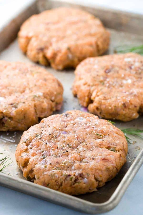 Four lightly seasoned salmon patties on a sheet pan ready to be grilled