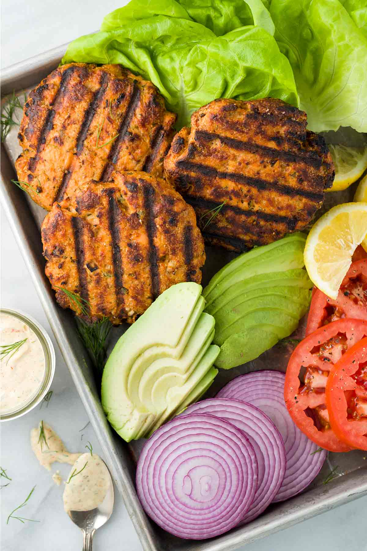Salmon patties with dark grill lines on a table with avocado, onions, bibb lettuce and tomato