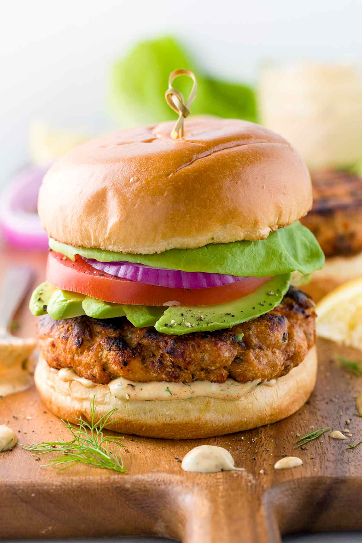 Salmon burgers with lemon dill sauce takes the seafood sandwich to the next level. Healthy protein grilled to perfection and topped with lettuce, tomato, onions, and avocado.