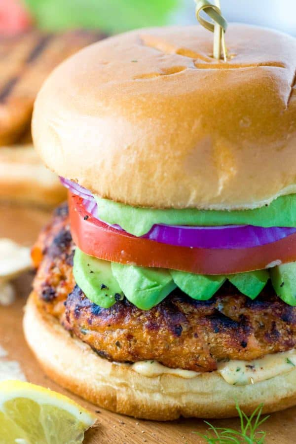 Grilled salmon burger with on a cutting board with a tooth pick holding the sandwich together