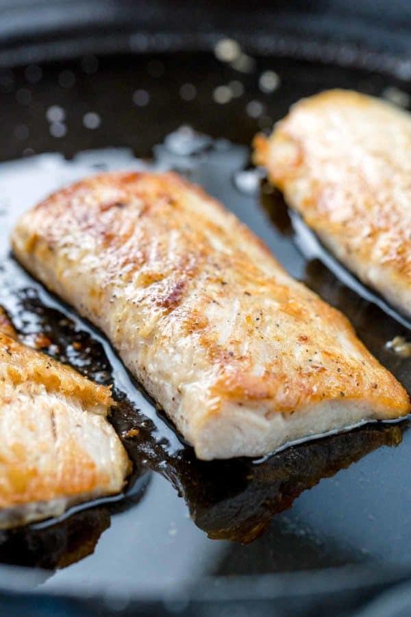 Mahi Mahi fish fillets searing in oil on a cast iron skillet