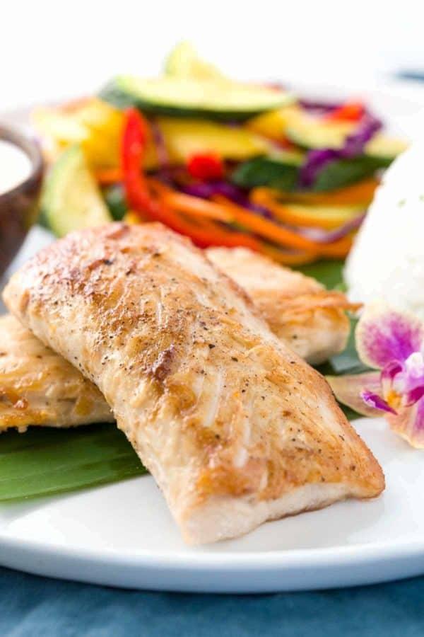 Mahi Mahi fish pan fried with crispy skin on a plate with steamed vegetables