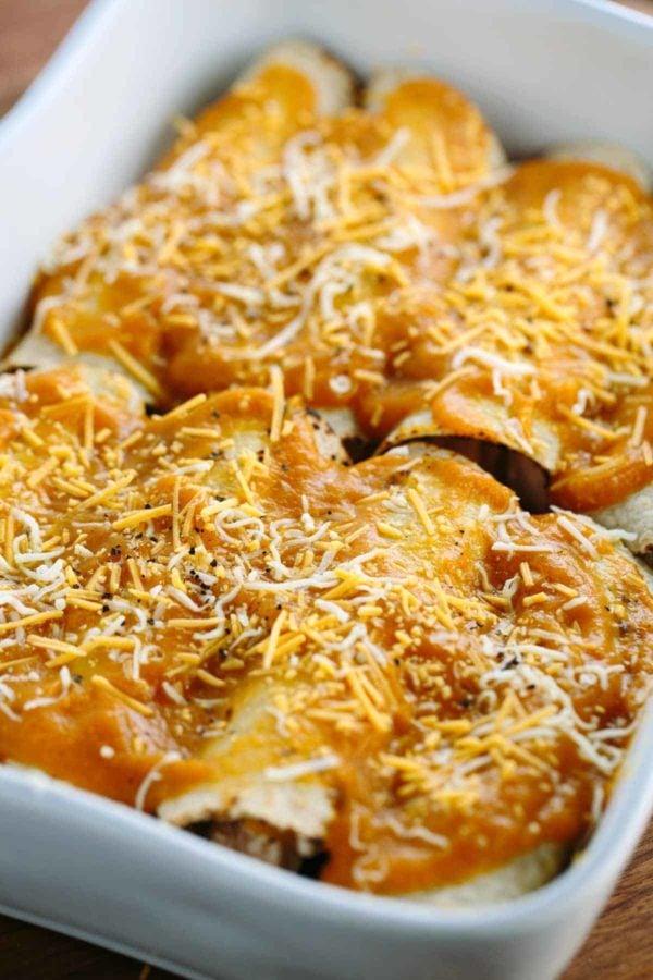 Chicken enchiladas with pumpkin sauce in a casserole dish before baking