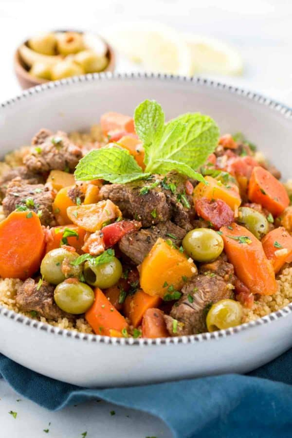 White bowl of Moroccan lamb stew with olives and carrots