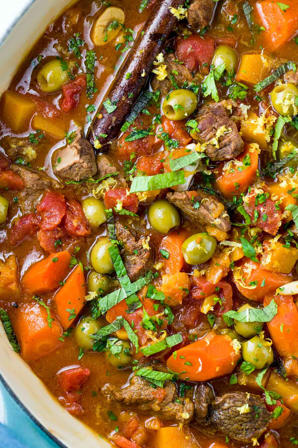 A big cast iron pot with chunks of lamb shoulder, vegetables and olives.
