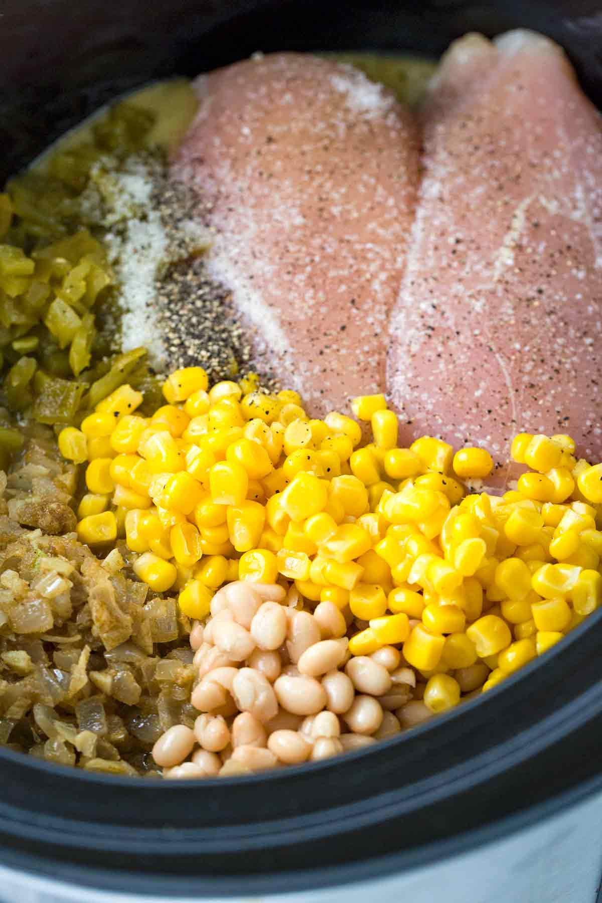 A crockpot with whole roasted jalapenos, tender beans, corn, and seasoned chicken breast.