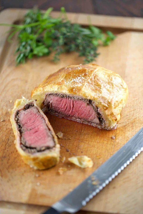 Beef Wellington sliced open on cutting board