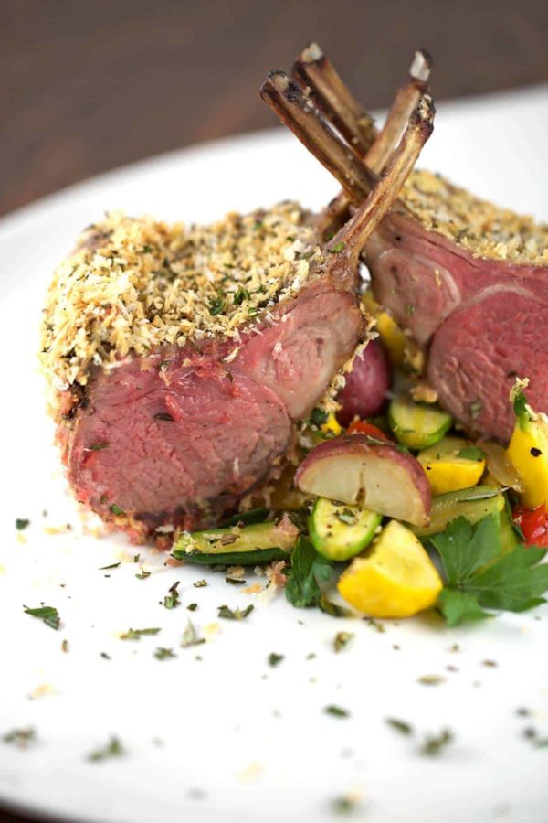 Herb crusted rack of lamb on a plate with vegetables