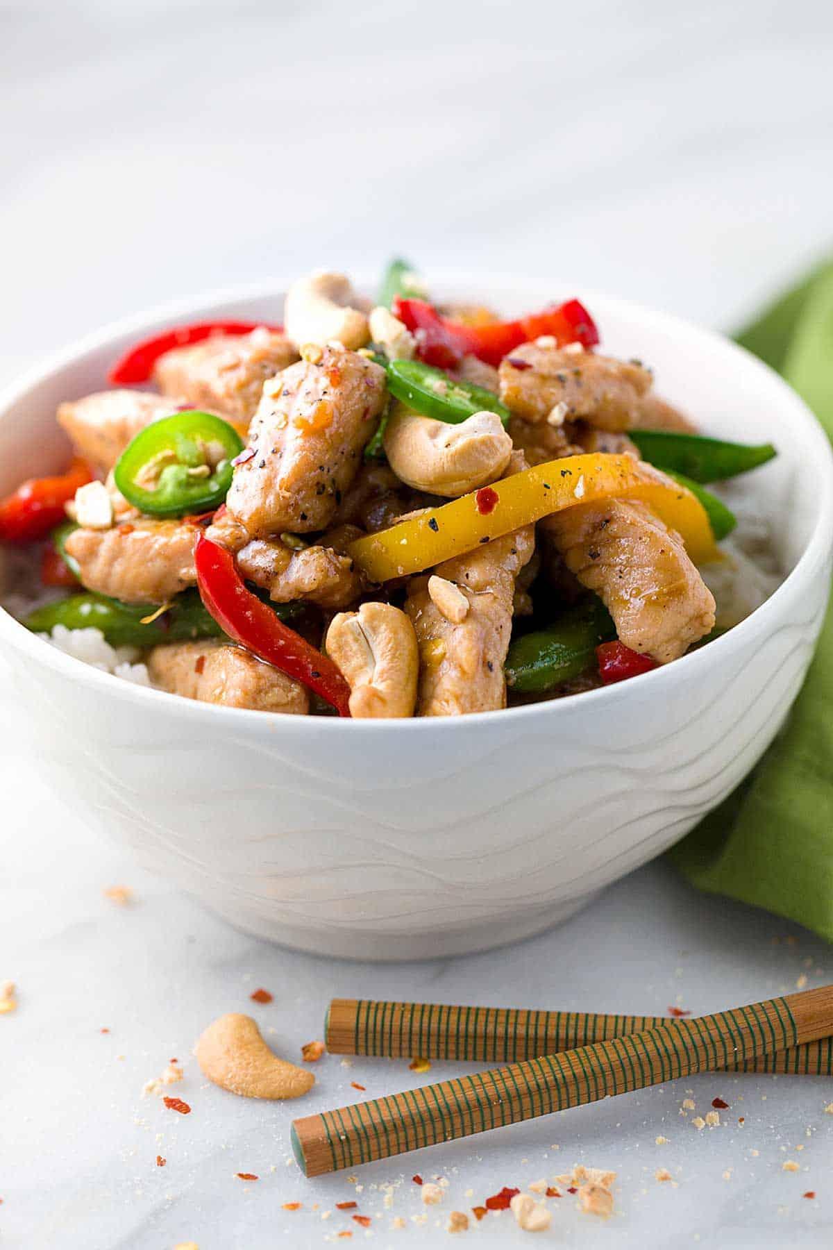 Pork stir-fry in a white bowl with chop sticks