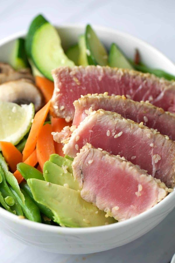 close up of sesame crusted ahi in a bowl with avocado and slices of carrots