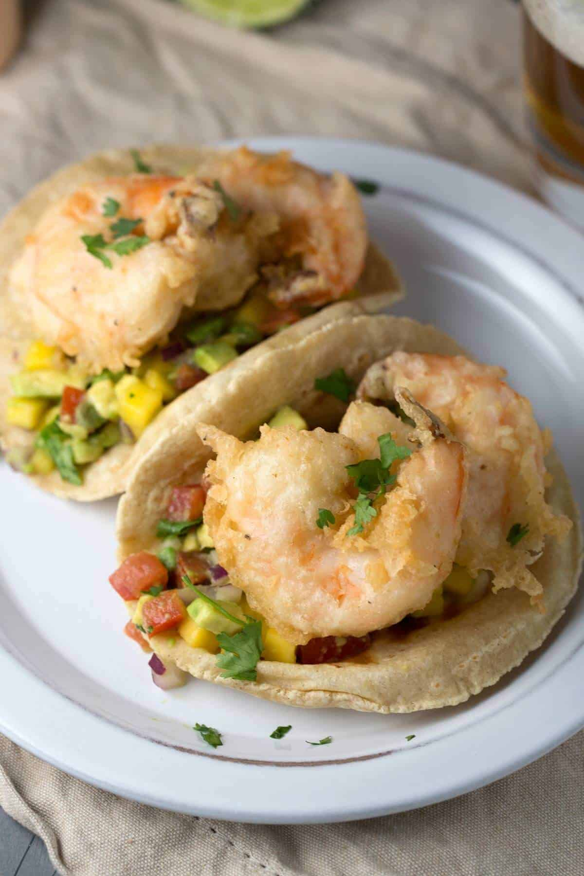 two beer-battered shrimp tacos on a plate