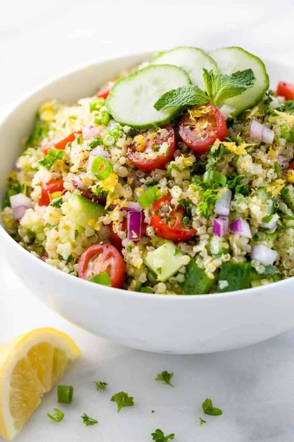 White bowl of quinoa tabbouleh with sliced cucumbers and cherry tomatoes on top