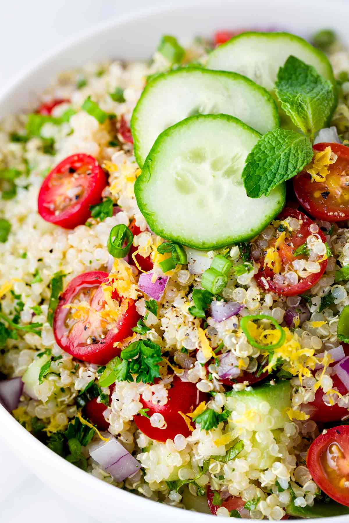 Close up photo showing quinoa tabbouleh in a white serving bowl