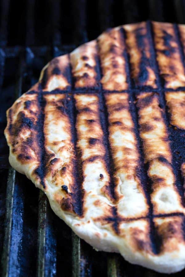 pizza dough cooking on a barbecue with grill marks