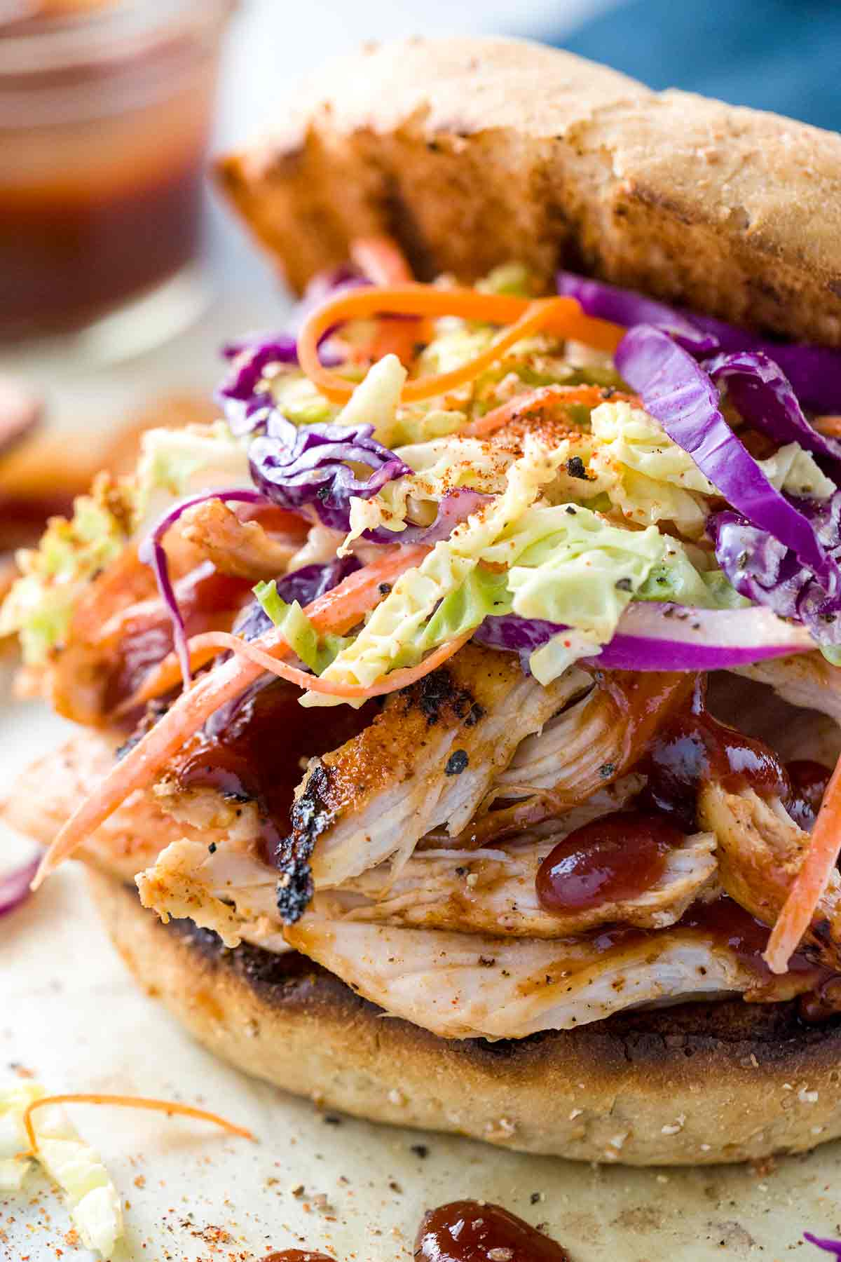 A sandwich with homemade coleslaw piled on top of pieces of pulled chicken