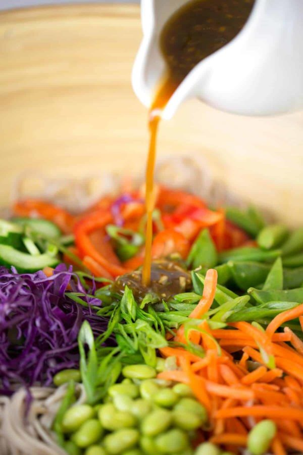 Pouring soy citrus dressing over Asian soba noodles