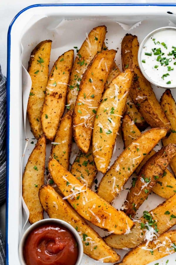 Serving platter with freshly baked potato wedges and two types of dipping sauces