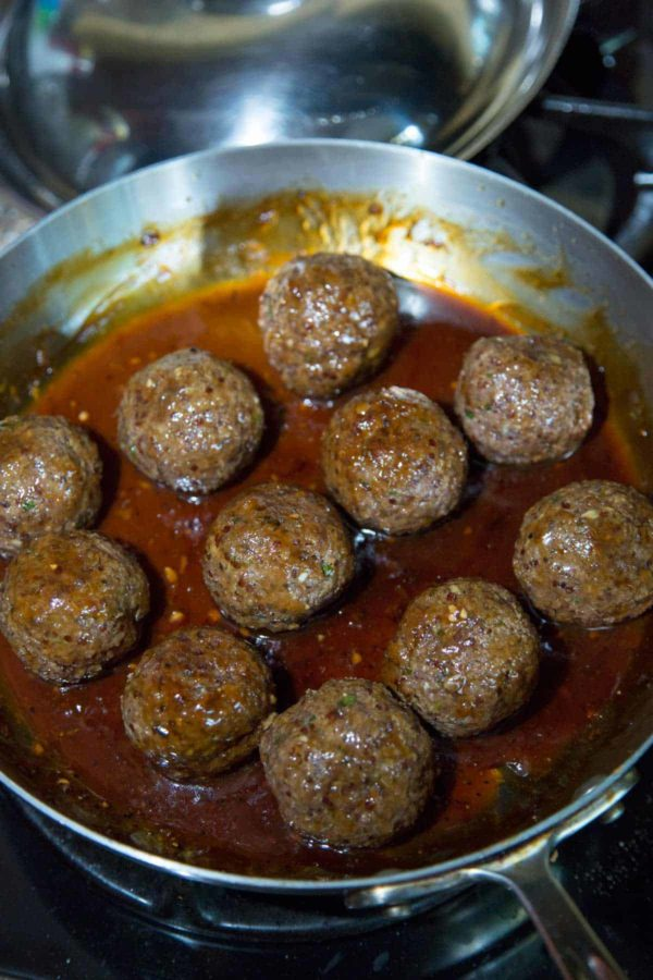 Meatballs marinating in a pan with spicy orange sauce