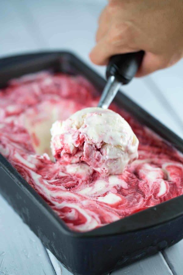 Scooping out some homemade raspberry no-churn ice cream