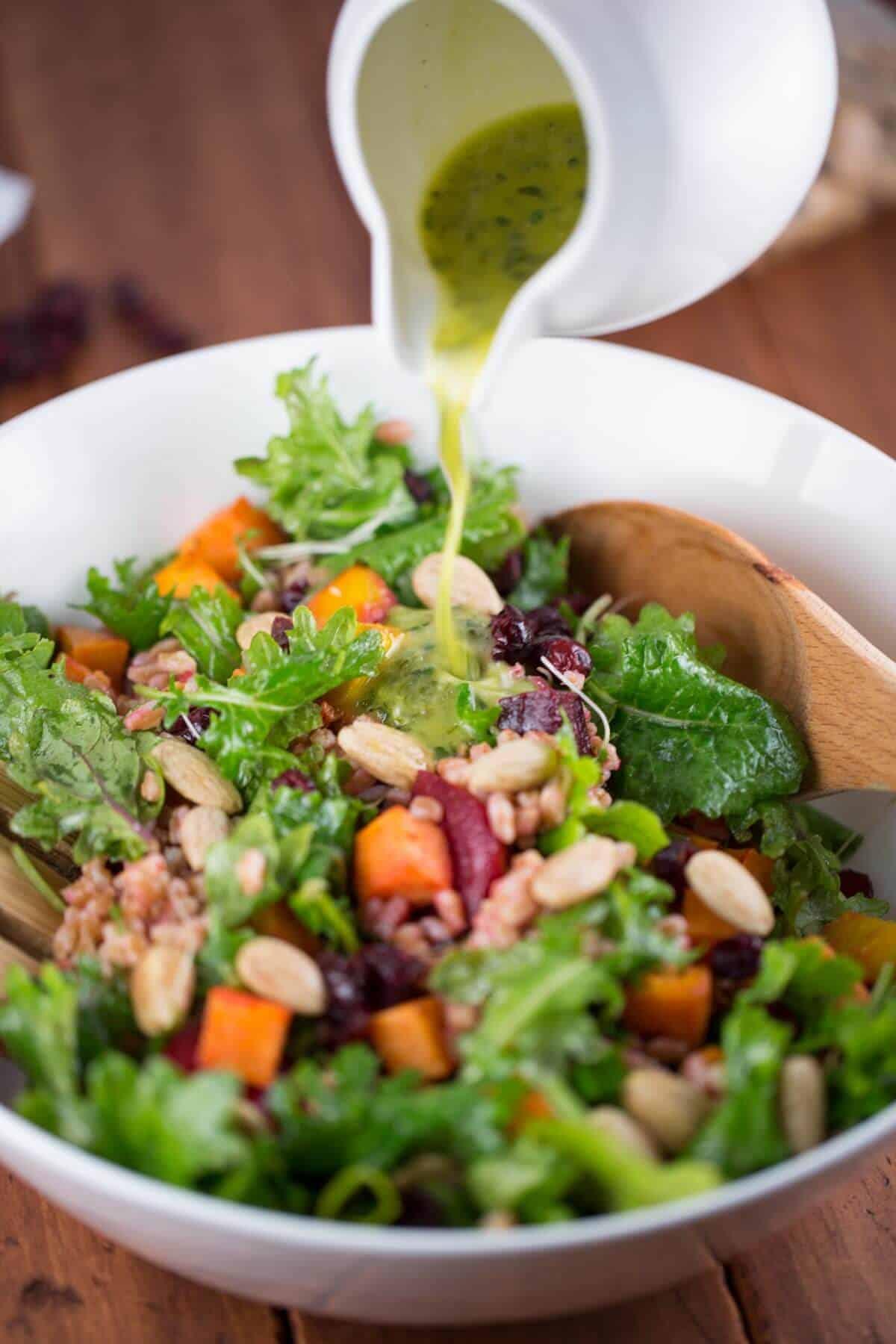 Pouring homemade dressing over farro salad | jessicagavin.com