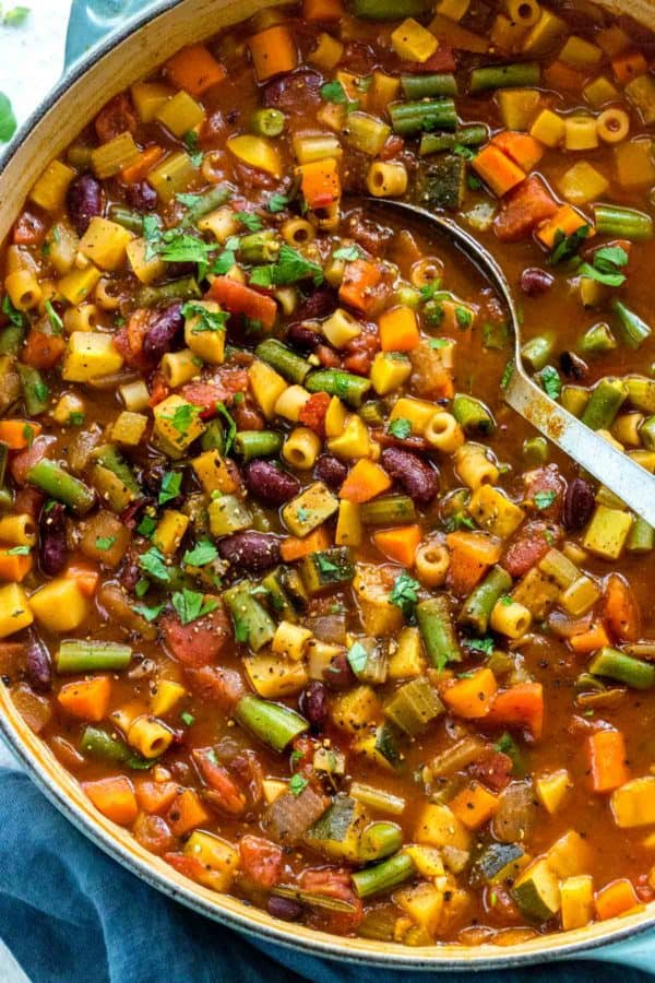 A big colorful pot of classic Italian minestrone soup being mixed with a spoon