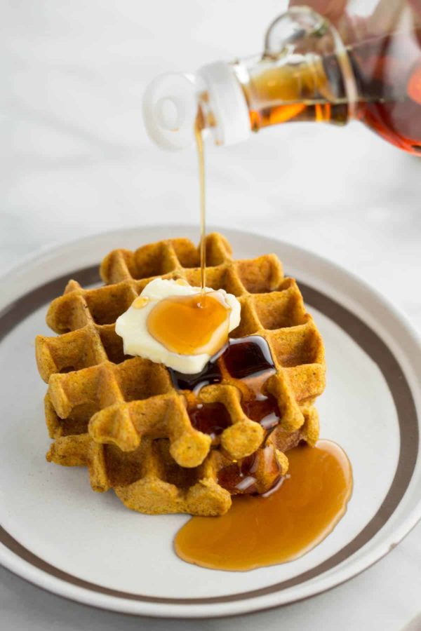 pouring-maple-syrup-over-pumpkin-waffles