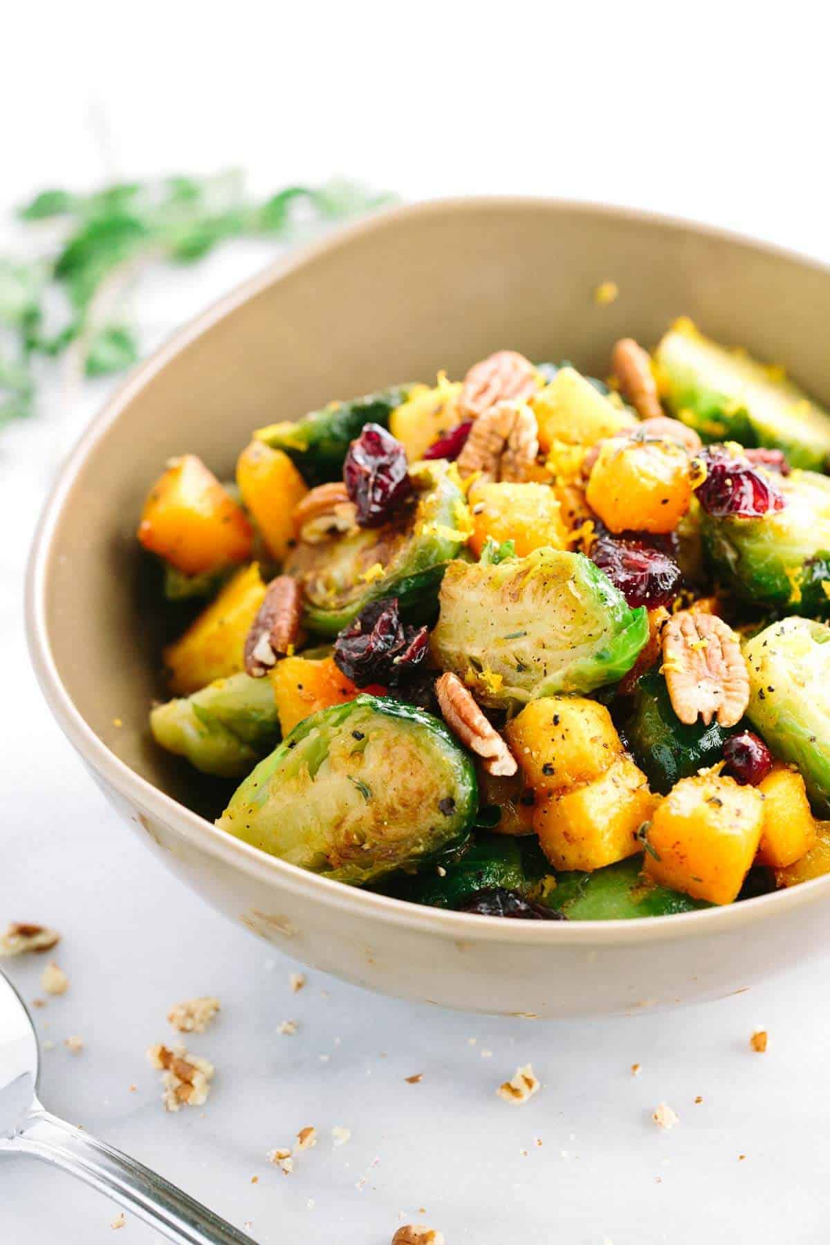 Honey Orange Glazed Brussels Sprouts with Butternut Squash - A delicious and easy recipe tossed with sweet tangy sauce, cranberries and crunchy pecans | jessicagavin.com