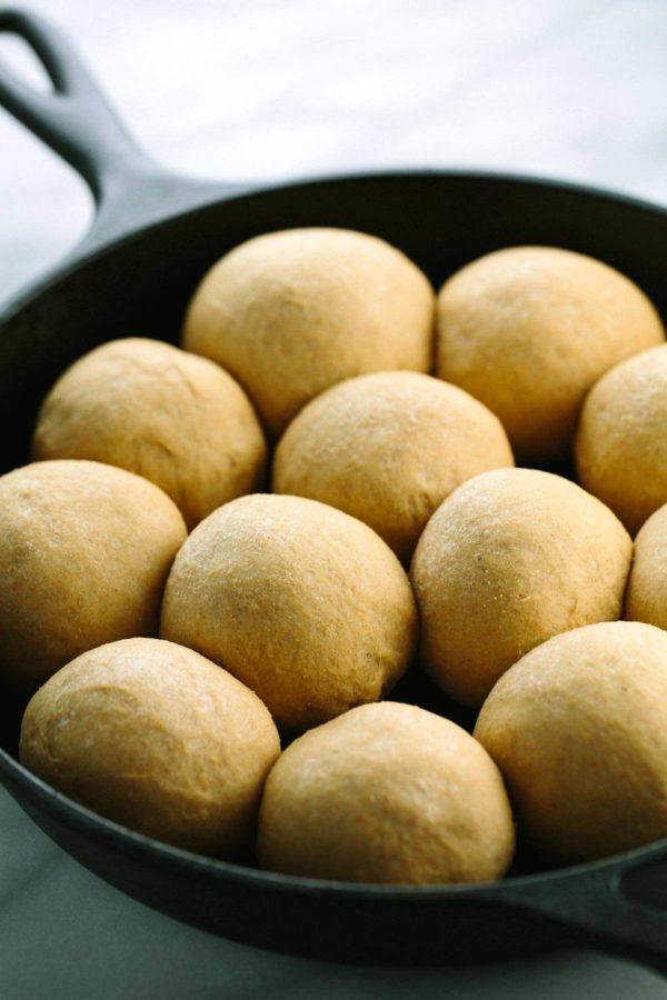dough balls rising inside a cast iron pan