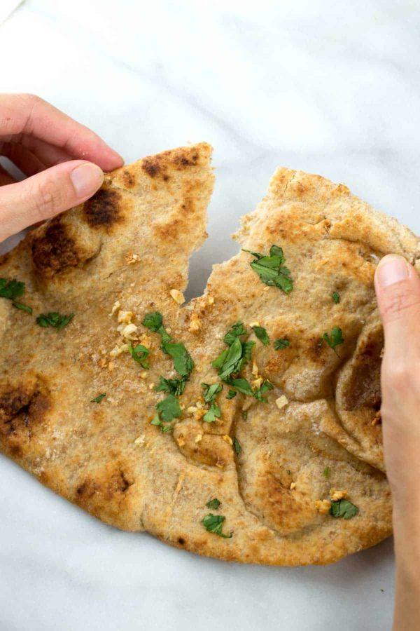 Oven baked garlic naan being split open to eat