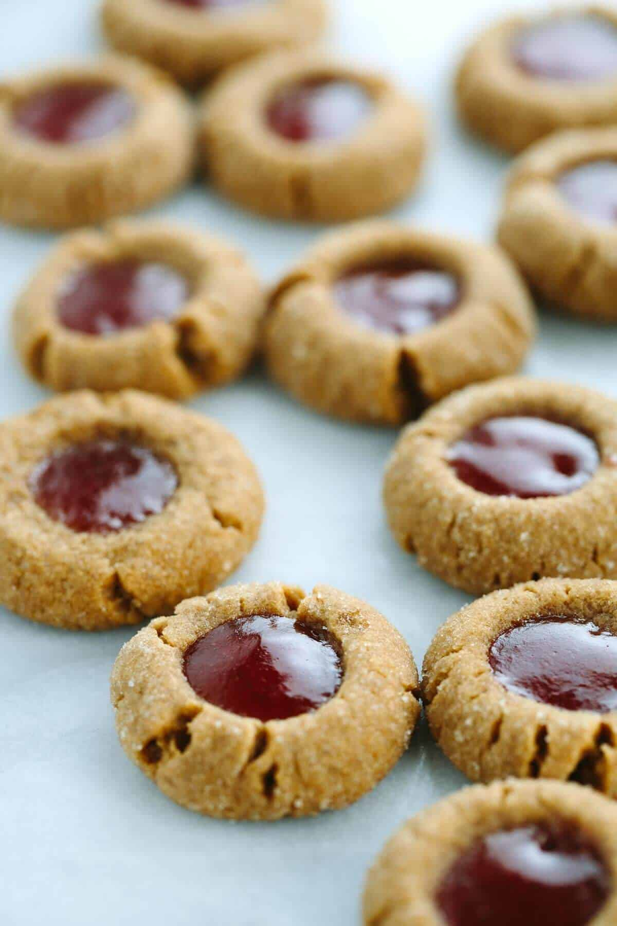 Flourless Peanut Butter and Jelly Thumbprint Cookies - this recipe is super easy to make, just one bowl and six ingredients! These PB&J cookies melt in your mouth and have a rich peanut flavor. | jessicagavin.com