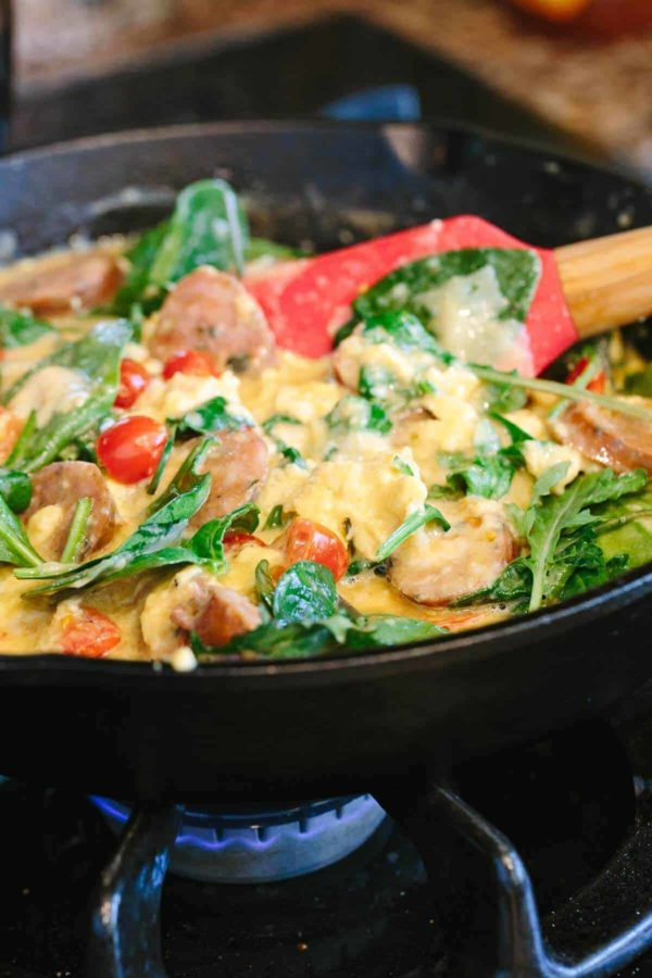 Cooking egg scramble with vegetables and sausage in a skillet